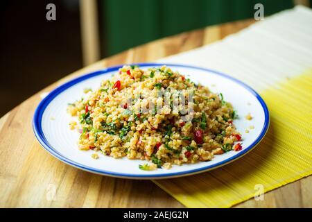 Hausgemachte veganes Essen (vegane) von Bulgur Salat Müsli mit frischem Gemüse, Spinat, Avocado, Gewürzen und Olivenöl. Gesund essen Bio eco-Konzept. - Stockfoto