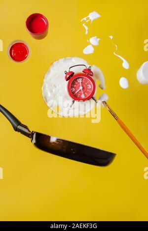 Spiegelei und Pfanne mit einem roten Watch, Farbe Gläser und sprühen Farben und Pinsel malen Sie schweben in der Luft.