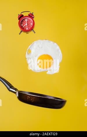 Zeit für das Frühstück. Ein Spiegelei und eine Pfanne mit einer Uhr schweben in der Luft auf einem gelben Hintergrund