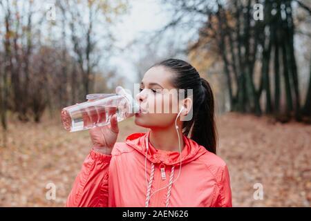 Junge sport Frau trinkt frisches Wasser aus der Flasche im Herbst Park. Sport Lifestyle.