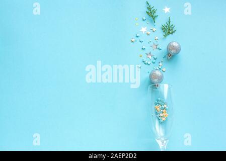 Weihnachtsfeier Hintergrund. Champagner Glas mit cofetti Sterne, Tannenzweigen und Kugeln auf Blau pastell Hintergrund. Urlaub, Party und Feier - Stockfoto