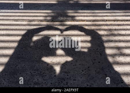 Silhouette von ein paar mit ihren Köpfen zusammen bilden eine Herzform mit ihren Armen wirft einen Schatten auf den Bürgersteig mit Gitter Overhead - Stockfoto