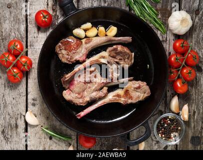 Gebratenes Lamm Rippen mit Rosmarin, Tomaten und auf Pan auf einem dunklen alten rustikalen Holzmöbeln Hintergrund Knoblauch, Ansicht von oben - Stockfoto