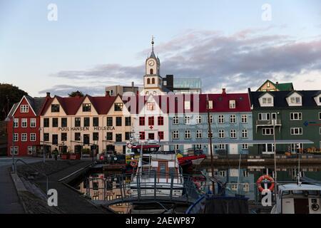 Tórshavn, Färöer Inseln - September 2019: Boote in einem Hafen vor der Kathedrale in der Dämmerung - Stockfoto