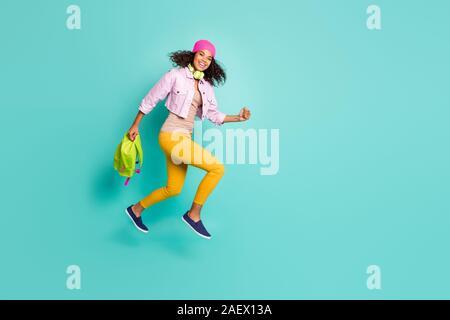 Volle Länge Körpergröße Seite Profil Foto von Casual positive springen laufen Schule Mädchen streben nach der pädagogischen Komplex auf Zeit in Gelb zu kommen - Stockfoto