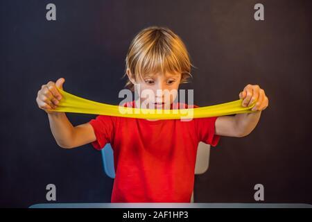 Junge spielt handgemachte Spielzeug namens Schleim. Kind Spiel mit Schleim. Kid squeeze und Stretching Schleim - Stockfoto