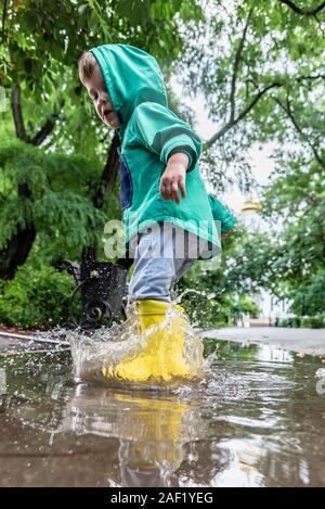 Little Boy in einer Pfütze in Gummistiefeln springen - Stockfoto