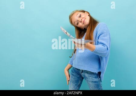 Junge europäische Mädchen, dass Geld in den Händen auf einem hellblauen Hintergrund - Stockfoto