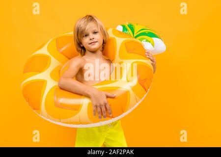 Europäische blonde Junge im gelben Badehose mit Schwimmen Kreis Ananas orange hinterlegt - Stockfoto