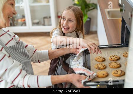 Fröhlicher junger Mädchen erreichen für die Cookies - Stockfoto