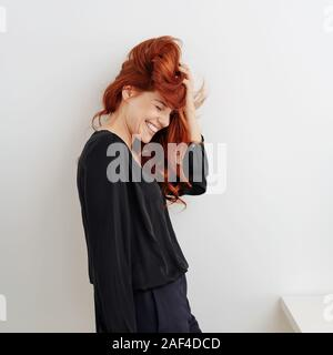 Spaß junge Frau mit zerzaustem Haar zu kichern, als sie ihre Hand zu halten - Stockfoto
