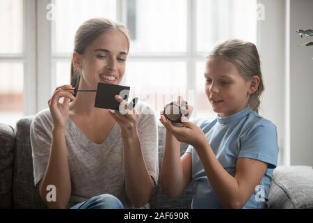 Junge Mutter und Tochter Make-up zu Hause gemeinsam entspannen - Stockfoto