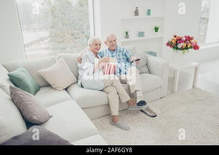 Zwei nette attraktive Heiter Heiter Ehegatten Spaß verbringen Freizeit Video serielle Komiker Kanal im Licht innen weiß Wohnzimmer - Stockfoto
