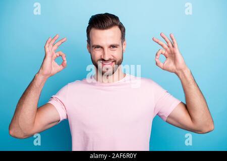 Nahaufnahme Foto von attraktiven Kerl halten sich an den Händen, okey Symbole zum Ausdruck Vereinbarung toothy Lächeln tragen casual Rosa t-shirt isoliert Blau - Stockfoto