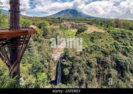 Indonesische Landschaft in Central Java. Blick auf den Vulkan Merapi und der Air Terjun Kedung Kayang Wasserfall - Stockfoto