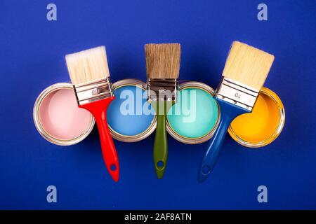 Vier offene Farbdosen mit Bürsten auf blauem Hintergrund. Gelb, Blau, Pink, Türkis Farben. Ansicht von oben.