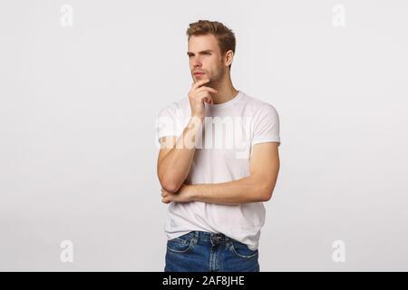 Intelligente und Kreative, durchdachte Schöne reife Blondine Geschäftsmann in casual Outfit, in Gedanken, Schielen und runzelte die Stirn und Kinn berühren, - Stockfoto