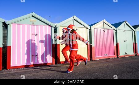 Brighton UK 14. Dezember 2019 - Mandy und Sue aus dem Lancing Adler Läufer melden Sie Hunderte an der Brighton Santa Dash nehmen an einem windigen Tag am Meer entlang helfen, Geld für die Liebe, die die Rockinghorse fundraising Arm der Royal Alexandra Children's Hospital zu erhöhen. Foto: Simon Dack/Alamy leben Nachrichten - Stockfoto