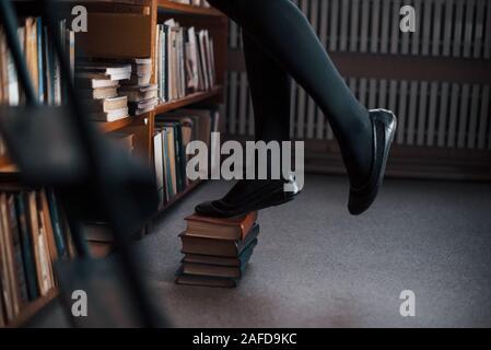 Stehend auf Bücher und versuchen, obere der Regale zu erreichen. Studentin ist in der Bibliothek. Konzeption von Bildung - Stockfoto