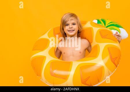 Europäische blonde Junge im gelben Badehose mit Schwimmen Kreis Ananas auf ein orange Wand - Stockfoto