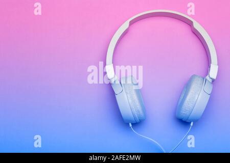 Musikalische Kopfhörer auf einem farbigen Blau und Rosa Hintergrund. Ästhetik Retro 80s und minimalen Begriff. - Stockfoto