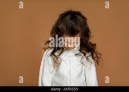 Runzelte die Stirn, kleines Kind Mädchen in weißen Pullover. Menschliche Gefühle und Mimik - Stockfoto