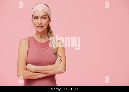 Taille bis Portrait von aktiven reife Frau an der Kamera schaut beim Stehen mit Waffen gegen Pastell rosa Hintergrund gekreuzt, kopieren Raum - Stockfoto