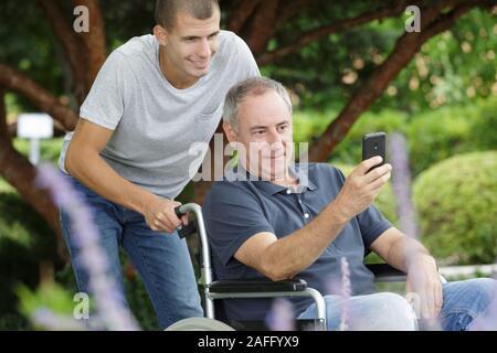 Ein erwachsener Sohn mit dem Vater im Rollstuhl im Freien - Stockfoto