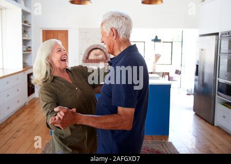Senior Paar zu Hause Tanzen in der Küche zusammen - Stockfoto