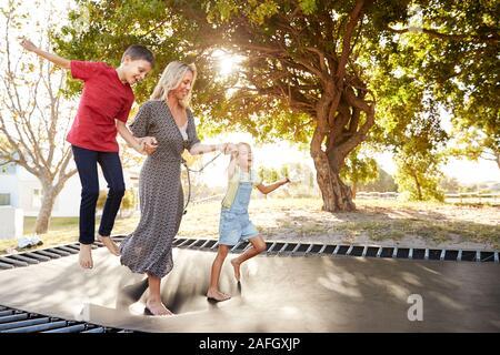Mutter spielt mit Kindern auf Outdoor Trampolin im Garten - Stockfoto