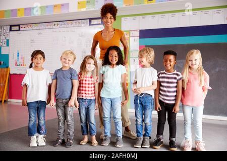 Portrait von Grundschülern im Klassenzimmer mit Lehrerin stehend