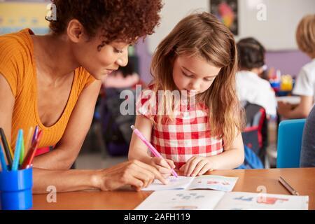 Grundschullehrer, die weiblichen Schüler Eins zu Eins Unterstützung im Klassenzimmer