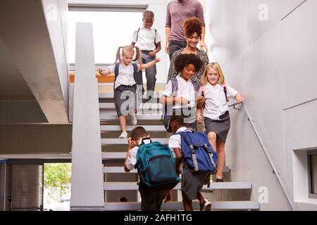 Lehrer und Schüler zu Fuß über Treppen in den Beschäftigten Volksschule Korridor