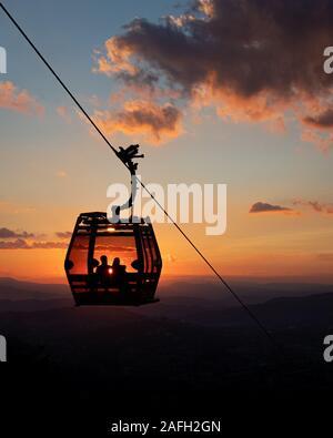 Eine vertikale Silhouette schoss der Menschen innerhalb einer Seilbahn Wagen bei Sonnenuntergang - Stockfoto