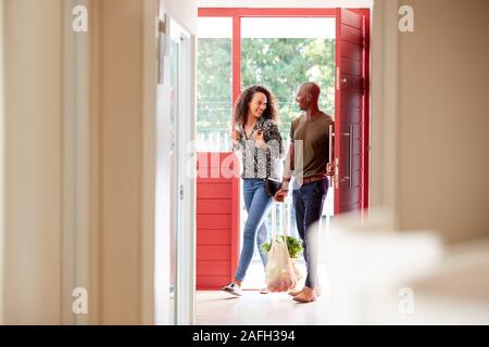 Paar Heimweg von Shopping Lebensmittel, die in Kunststoff freien Beuteln - Stockfoto