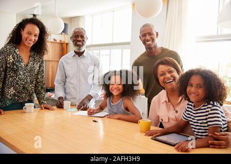 Portrait von Großeltern am Tisch sitzen mit Enkelkindern Spielen auf Besuch bei der Familie - Stockfoto