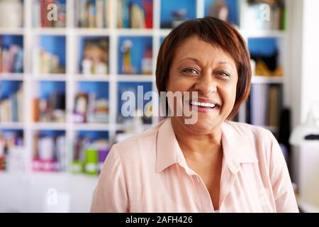 Portrait von lächelnden reife Frau im Home Office durch Bücherregal - Stockfoto