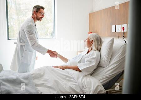 Chirurg besuchen und das Händeschütteln mit Reife Weibliche Patienten im Krankenhaus Bed - Stockfoto