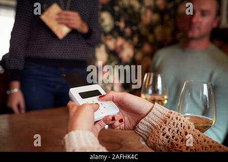 In der Nähe von Kunden im Restaurant Eingabe der PIN-Nummer in Kreditkarte Terminal - Stockfoto