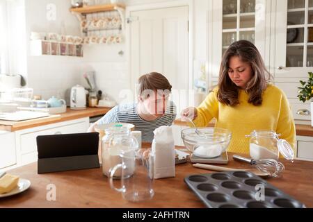 Junge Abstiegsyndrom Paar folgende Rezept auf digitalen Tablet zu backen Kuchen in der Küche zu Hause. - Stockfoto