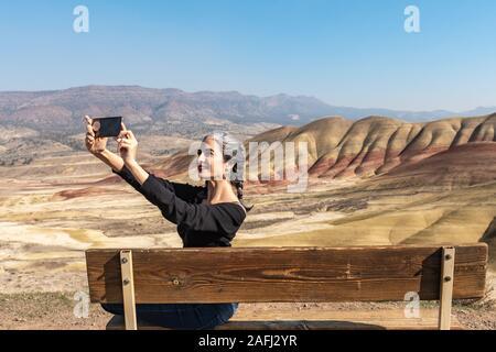 Eine junge Brünette mit grauen Strähnen macht selfies sitzen auf einer Bank in Painted Hills mit Blick auf