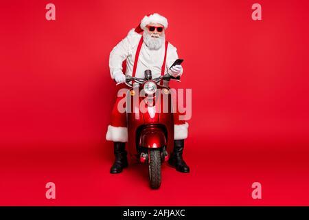 Portrait von Nizza attraktive Bärtigen heiter fröhlichen Santa tragen cap Hut sitzen auf Motorrad mit Zelle, Aufträge über Helle, lebendige isoliert - Stockfoto