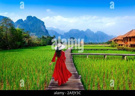 Junge Frau zu Fuß auf Holz- Pfad mit grünen Reisfeldern in Vang Vieng, Laos. - Stockfoto