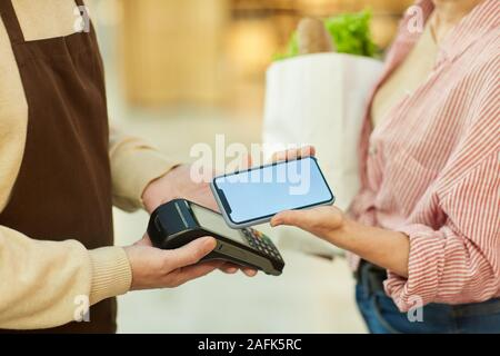 Nahaufnahme des unkenntlich moderne Frau Zahlung über NFC beim Einkaufen bei Farmers Market, Kopie Raum - Stockfoto