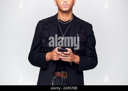 In der Nähe von Studio Geschossen von Kausal gekleideter junger Mann mit Handy - Stockfoto