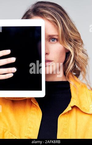 Studio Portrait von Sorgen junge Frau mit Gesicht mit digitalen Tablet - Stockfoto