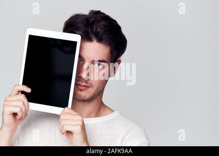 Studio Portrait von Sorgen junger Mann mit Gesicht mit digitalen Tablet - Stockfoto