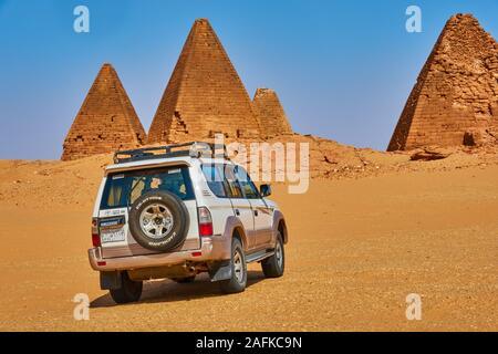 Karima, Sudan, Ca. Februar 8., 2019: Off-road-Fahrzeug in der Wüste vor der beeindruckenden Pyramiden von Kamira, Sudan - Stockfoto