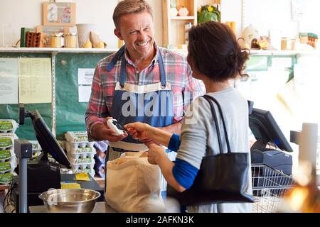 Kunden an der Kasse von organischen Farm Shop, kontaktloses Bezahlen - Stockfoto