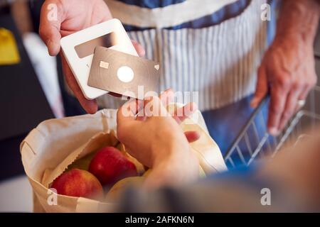 Nahaufnahme des Kunden an der Kasse von organischen Farm Shop, kontaktloses Bezahlen - Stockfoto